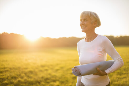 Smiling senior woman holding yoga mat on rural meadow at sunset - DIGF05479