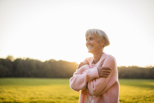 Smiling senior woman standing on rural meadow at sunset - DIGF05482