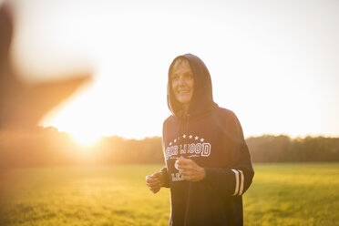 Smiling senior woman wearing a hoodie standing on rural meadow at sunset - DIGF05485