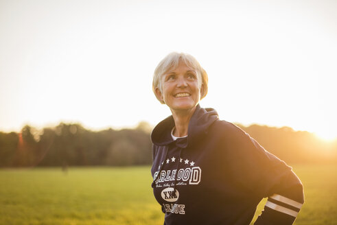 Smiling senior woman wearing a hoodie standing on rural meadow at sunset - DIGF05488