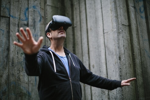 A middle aged man wearing a virtual reality headset. - MINF09569