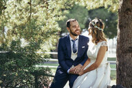 Happy bridal couple holding hands in a park - JSMF00563