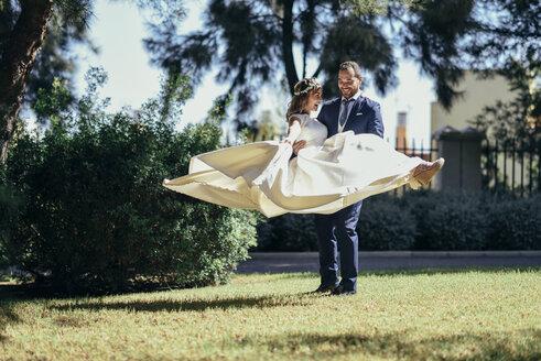 Bridal couple enjoying wedding day in a park - JSMF00566