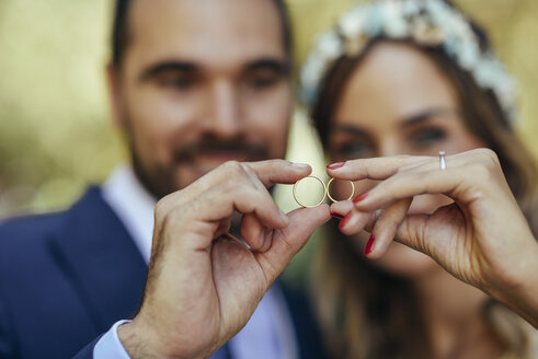 Happy bridal couple showing their wedding rings, close-up - JSMF00569
