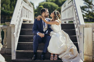 Bridal couple sitting on stairs in a park - JSMF00575