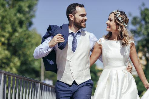 Happy bridal couple enjoying their wedding day in a park - JSMF00578
