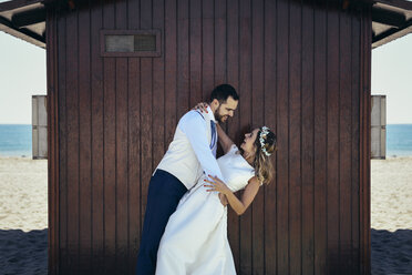 Bridal couple enjoying romantic moments in front of a beach hut - JSMF00581