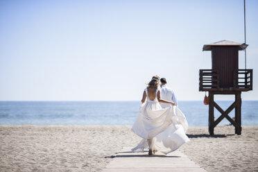 Back view of bridal couple enjoying  wedding day walking on the beach - JSMF00584
