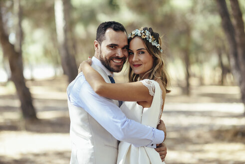 Portrait of happy bridal couple standing head to head in pine forest - JSMF00593