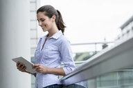 Smiling young businesswoman using digital tablet outdoors - BMOF00076