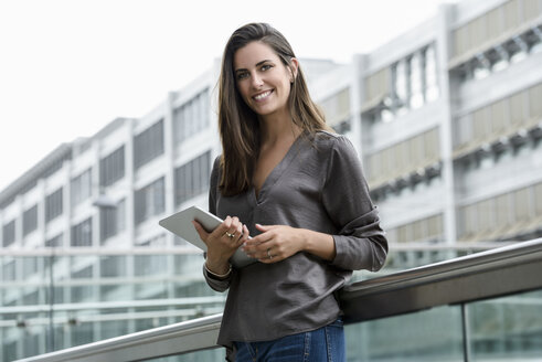 Portrait of smiling young businesswoman with digital tablet - BMOF00079