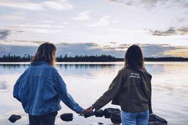 Girl friends looking at Lake Inari,Finland,  holding hands - RSGF00098