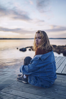 Young woman sitting at lake Inari, looking at camera, Finland - RSGF00101