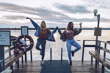 Two girl friends standing on one leg on a pier at Lake INari, Finland - RSGF00107