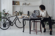 Mid adult woman working in her home office, using laptop - BOYF00892