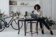 Mid adult woman working in her home office, using laptop - BOYF00895