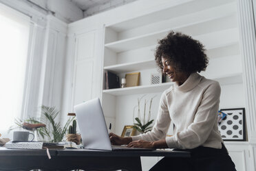 Mid adult woman working in her home office, using laptop - BOYF00901
