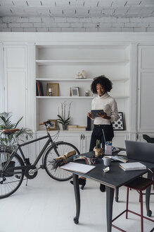 Mid adult freelancer standing in her home office, using digital tablet - BOYF00907