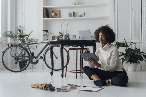 Disigner sitting on ground of her home office, using digital tablet - BOYF00913