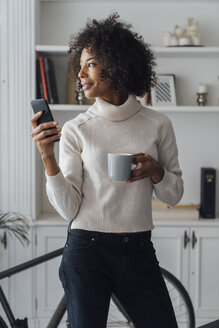 Mid adult freelancer standing in her home office, using smartphone, holding coffee cup - BOYF00922