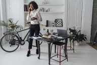 Mid adult freelancer standing in her home office, drinking coffee, talking on the phone - BOYF00925