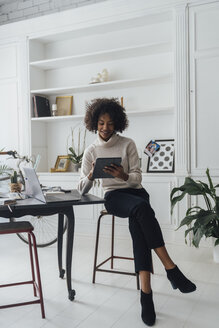 Mid adult freelancer sitting at her desk, working with laptop and digital tablet - BOYF00931