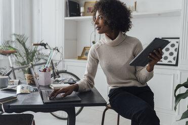 Mid adult freelancer sitting at her desk, working with laptop and digital tablet - BOYF00934