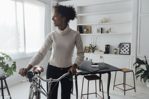 Mid adult woman leaving her home office, pushing bicycle - BOYF00943