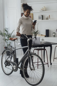 Mid adult woman leaving her home office, pushing bicycle, using smartphone - BOYF00946