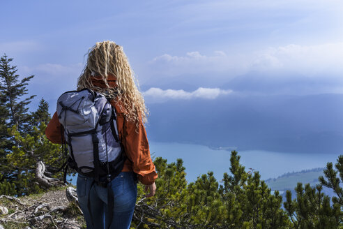 Young woman hiking in the Bavarian mountains, looking at Lake Walchensee - TCF05908