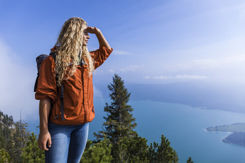 Young woman hiking in the Bavarian mountains, looking at Lake Walchensee - TCF05914