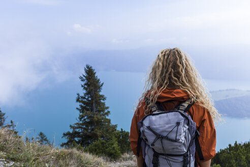 Young woman hiking in the Bavarian mountains, looking at Lake Walchensee - TCF05917