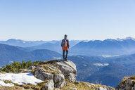 Germany, Garmisch-Partenkirchen, Alpspitze, Osterfelderkopf, female hiker on viewpoint looking at view - TCF05936