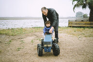 Father helping a baby girl to drive a toy tractor next to the rice fields - GEMF02502