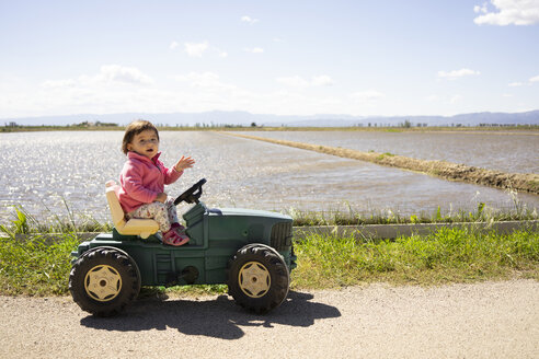 Baby girl driving a toy tractor next to the rice fields - GEMF02514