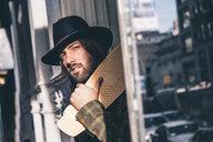 USA, New York City, portrait of bearded man with skateboard wearing black hat - OCMF00096