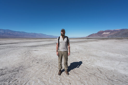USA, California, Death Valley, man standing in desert - KKAF02960
