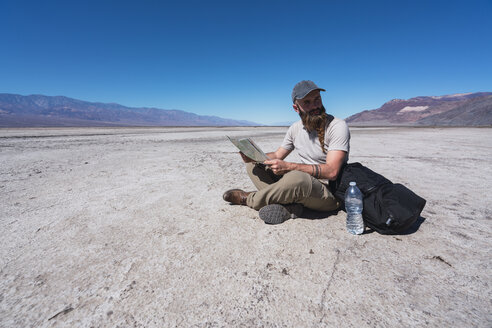USA, California, Death Valley, man sitting on ground in the desert with map having a rest - KKAF02963