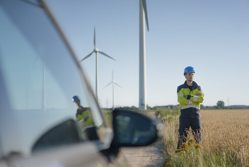 Engineer standing in a field at a wind farm - GUSF01306