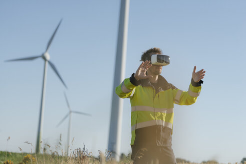Engineer standing in a field at a wind farm wearing VR glasses - GUSF01309