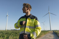 Engineer on field path at a wind farm looking around - GUSF01315