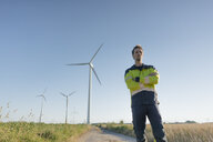 Engineer standing on field path at a wind farm - GUSF01318