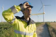 Portrait of an engineer with party blower at a wind farm - GUSF01321