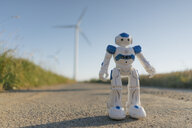 Robot standing on field path at a wind farm - GUSF01324