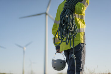 Close-up of technician at a wind farm with climbing equipment - GUSF01327