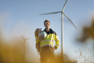 Technician standing in a field at a wind farm with climbing equipment - GUSF01330