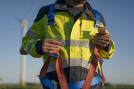 Close-up of technician at a wind farm putting on climbing harness - GUSF01336