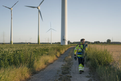 Technician walking on field path at a wind farm with climbing equipment - GUSF01339