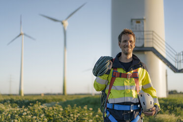 Portrait of smiling technician standing at a wind farm with climbing equipment - GUSF01342