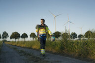 Technician walking on field path at a wind farm with climbing equipment - GUSF01345
